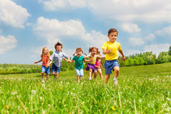 Running kids in green field during summer. Running happy kids in green field during summer time Royalty Free Stock Photos