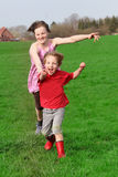 Running kids. Two happy kids running on a green meadow stock photo