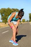 Running knee injury and pain. Running sport knee injury. Woman runner in pain while training for marathon in country road. Caucasian female athlete Royalty Free Stock Photo