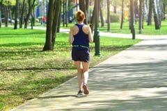 running La femme active court la croix en parc d'?t? photos stock