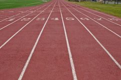 Lanes of a running track. Running lanes on a red track with white numbers and lines with green grass on both sides royalty free stock images