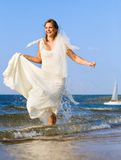 Running laughing bride on the sea Royalty Free Stock Image