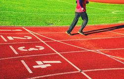 Running legs and shadow of a male athlete running on track. Running legs and moving shadow of a male athlete running on track of outside stadium stock photos