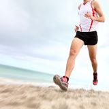 Running legs and shoes. Of runner jogging on beach. Caucasian sport man training for marathon royalty free stock photography