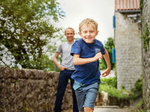 Running little boy portrait. Little blond boy's running away from his father Stock Images