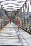 Running little girl on pedestrian bridge Stock Images