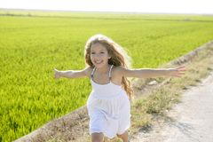 Running little happy girl in meadow. Running open arms little happy girl green meadow field Royalty Free Stock Photo