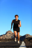 Running - male runner. Man sprinting during outdoor workout training session. Male caucasian athlete running on road in nature Stock Image
