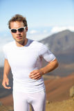 Running man. Male runner jogging outside in mountain landscape doing trail running in training for marathon race. Fit male fitness athlete in outdoor workout Royalty Free Stock Images