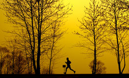 Running man. A running man silhouette in golden background Stock Images