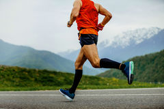 Running man athlete. Compression socks on background mountains and green forest stock photo