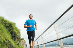 Running man. Attractive man running on a wooden walkway next to the sea. Daily training Stock Photos