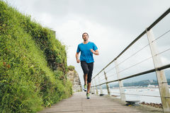 Running man. Attractive man running on a wooden walkway next to the sea. Daily training Royalty Free Stock Photos