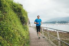 Running man. Attractive man running on a wooden walkway over the sea. Daily training Stock Photos