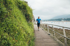 Running man. Attractive man running on a wooden walkway over the sea. Daily training Royalty Free Stock Photos