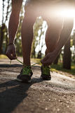 Running man closeup of running shoes on sunset or sunrise. Runner feet. Stock Photos