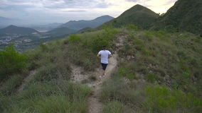 Running man exercising on mountain forest trail at sunset. Male run, work out