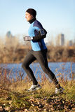 Running man jogging in autumn to music on phone. Running man jogging in autumn listening to music on smart phone. Runner training in warm outfit on cold day. Fit stock photos