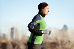 Running man jogging in autumn to music on phone. Running man jogging in autumn listening to music on smart phone. Runner training in warm outfit on cold day. Fit Stock Photo
