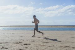 Running man jogging on beach.Muscular male runner training outside working out. Running man jogging on beach.Muscular male runner training outside working out Royalty Free Stock Photos