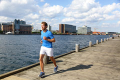 Running man jogging in modern city. Male runner exercising on Copenhagen boardwalk in Bryggen, Denmark Royalty Free Stock Photography