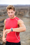 Running man looking at heart rate monitor. GPS watch. Runner listening to music in earphones wearing red compression t-shirt top Stock Image