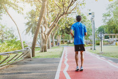 Running man. Male runner jogging during outdoor workout at public park.  Stock Photos