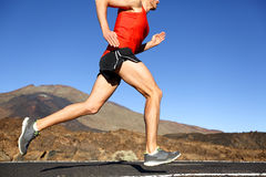 Running man - male runner training outdoors. Sprinting on mountain road in amazing landscape nature. Close up of fit handsome jogger working out for marathon Royalty Free Stock Photos