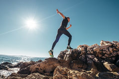 Running man. By the rocky sea cost Royalty Free Stock Photos