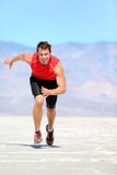 Running man - runner sprinting in desert. Nature. Fit athlete in fast sprint run at great speed towards camera. Male fitness model in amazing extreme desert Stock Photography