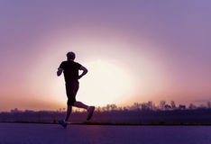 Running man silhouette in sunset time Stock Photos