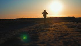 Running man silhouette in sunset time. Outdoor cross-country running. Athletic young man is running in the nature during stock footage
