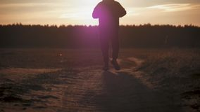Running man silhouette in sunset time. Outdoor cross-country running. Athletic young man is running in the nature during stock video