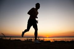 Running man silhouette in sunset time. Sport and active life concept. stock photo