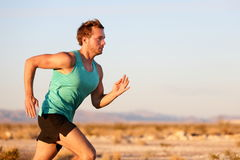 Running man sprinting cross country trail run. Male fit sport fitness model training for marathon outside in beautiful landscape. Caucasian handsome guy in his Royalty Free Stock Images