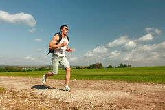 Running man sprinting cross on a trail. Male fit sport fitness model training for marathon outside in beautiful landscape Royalty Free Stock Photography