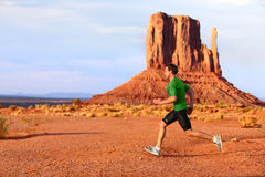 Running man sprinting in Monument Valley. Athlete runner cross country trail running outdoors in amazing nature landscape. Fit male sports model in fast sprint Royalty Free Stock Image
