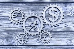 Running man with a suitcase, twirled gears, currency signs. On a wooden background. business. finance stock image