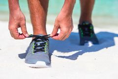 Running man tying running shoe laces on white Royalty Free Stock Photography