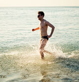 Running man in water of sea Stock Photos