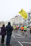Running marathon exercise sport healthy. A flag waving spectator encourages runners during a race, the Brighton half marathon in Sussex, England Stock Photos