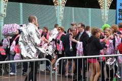 Running marathon exercise sport healthy. A runner wrapped in foil to keep warm after racing goes to collect his medal from officials at the Brighton half Stock Photography