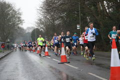 Running marathon fitness healthy lifestyle. A big group of runners taking part in the Surrey Half Marathon on a wet day Royalty Free Stock Photography