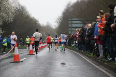 Running marathon fitness healthy lifestyle. A group of runners taking part in the Surrey Half Marathon on a wet day and supported by a big crowd of spectators Royalty Free Stock Photography