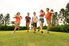 Running on meadow. Cheerful Asian young people running on meadow Stock Images