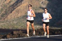 Running Men. Runner men running marathon training run on road in amazing mountain landscape. Two men jogging in sporty outfit Stock Image