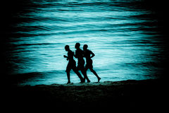 Running men. Three athletic men running along the beach Stock Photo