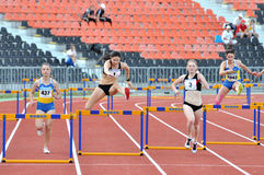 Running the 110 meter hurdles. Girls Royalty Free Stock Image
