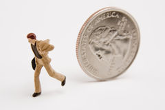 Running from Money Problems. Miniature businessman running from quarter Royalty Free Stock Photo