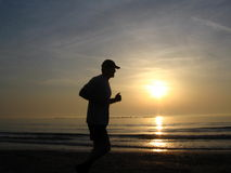 Running in the morning. Man running on the beach Stock Images